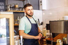 Portrait of a young male baristas at a bar counter near a coffee machine. Portrait of a handsome young man at a bar counter near a coffee machine. The barista Royalty Free Stock Images