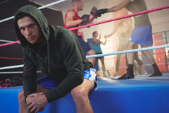 Portrait of young male boxer sitting on boxing ring at fitness studio Stock Images