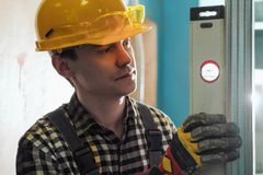 Portrait of a young male builder and repairman in a yellow helmet with level. royalty free stock photo