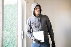 Male robber stealing a computer. Portrait of a young male burglar walking away unnoticed with a laptop computer Royalty Free Stock Photos