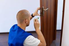Portrait Young Male Carpenter Repairing Door Lock Stock Photo