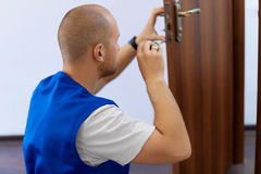 Portrait Young Male Carpenter Repairing Door Lock Stock Images