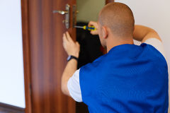 Portrait Young Male Carpenter Repairing Door Lock Royalty Free Stock Images