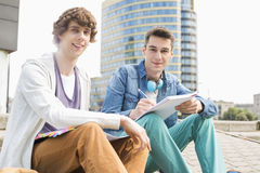 Portrait of young male college students studying on steps against building Royalty Free Stock Photos