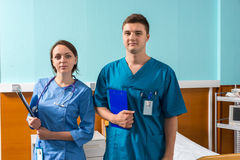 Portrait of young male and female doctor in uniform with phonend. Oscope on her neck holding clipboards while standing in the hospital ward. Healthcare concept Royalty Free Stock Photos