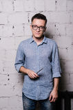 Portrait of young male hairdresser in glasses, posing with scissors, on gray brick wall background, front view. Portrait of handsome young man in jeans clothes Royalty Free Stock Photos