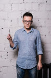 Portrait of young male hairdresser in glasses, posing with scissors, on gray brick wall background, front view, vertical. Portrait of handsome young man in jeans Stock Photography