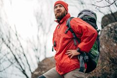 Young male hiking in mountains wearing red clothes exploring new place. Traveler bearded man trekking and mountaineering. Portrait of young male hiking in royalty free stock photography