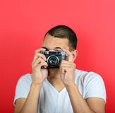 Portrait of young male holding vintage camera against red backgr Stock Images