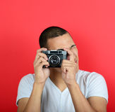 Portrait of young male holding vintage camera against red backgr Stock Photography
