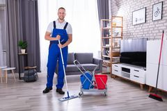 Portrait Of A Young Male Janitor. Portrait Of A Happy Male Janitor Standing In Living Room royalty free stock images