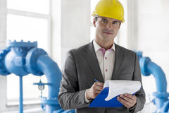 Portrait of young male manager writing on clipboard in industry Stock Photography