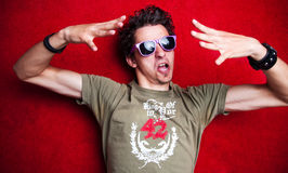 Portrait of a young male mode. L, showing an angry gesture with his hands, wearing purple sunglasses. Isolated on red background Stock Image