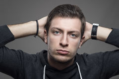 Portrait of young male model with hands behind head looking at camera Royalty Free Stock Image