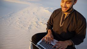 Portrait of young male Muslim student who prints on computer key. Educated Arab student or young scientist prints on laptop keyboard and working on article royalty free stock image