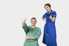 Portrait of young male patient with female nurse gesturing thumbs up against gray background Stock Photos