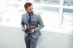 Portrait of young male professional worker dressed in corporate clothing holding touch pad while standing in office building Royalty Free Stock Photos