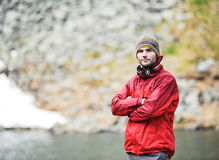 Portrait of young male in a red jacket. A portrait of a young happy man infront of a mountain lake Stock Photo