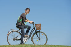 Portrait of young male student with a bicycle in park Royalty Free Stock Image
