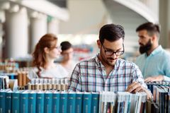 Portrait of young male student in library. Portrait of young male student in university library Royalty Free Stock Photos