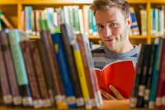 Male student reading a book in the library. Portrait of a young male student reading a book amid bookshelves in the college library Royalty Free Stock Photography
