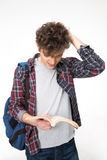 Portrait of a young male student reading book. Over gray background Stock Image