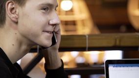 Portrait of young male student, who is talking to his friends while doing a phone call in stylish cafe. Man is sitting at the table and starts using his stock video