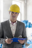 Portrait of young male supervisor holding clipboard in industry Royalty Free Stock Images