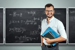 Portrait of a young male teacher on the background of the school blackboard. Teacher`s Day Knowledge Day back to school study