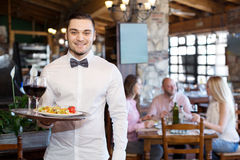 Portrait young male waiter. Portrait of a happy male waiter with a tray in his hand at the restaurant Stock Images