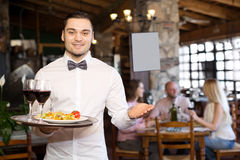 Portrait young male waiter. Portrait of a smiling male waiter with a tray in his hand at the restaurant Stock Image