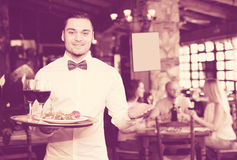 Portrait young male waiter. Portrait of a smiling male waiter with a tray in his hand at the restaurant Stock Photography
