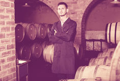 Portrait of young male wine maker in coat working in winery cell Stock Photo
