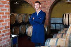 Portrait of young male wine maker in coat working in winery cell Royalty Free Stock Image