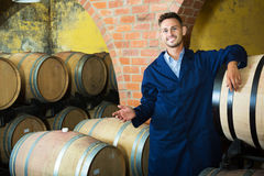 Portrait of young male wine maker in coat working in winery cell Stock Photos