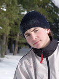Portrait of a young man. In a ski suit and a cap on the background of the winter forest Stock Photos