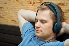This is a portrait of a young man. This is a photograph of laying young man listening music royalty free stock image