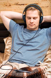 This is a portrait of a young man. This is a photograph of laying young man listening music stock photography