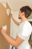 Portrait of young man aligning wall with putty Royalty Free Stock Images