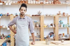 Potter in workshop. Portrait of young man in apron standing in workshop with handmade clay products and looking at camera Stock Image