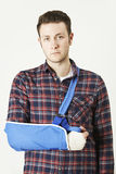 Portrait Of Young Man With Arm In Sling. Unhappy Young Man With Arm In Sling Stock Images