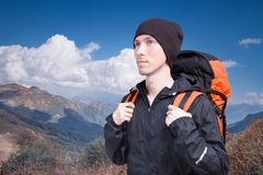 Portrait of young man with backpack on the background of a mountain landscape and a blue sky with white clouds. Mountain Stock Photos