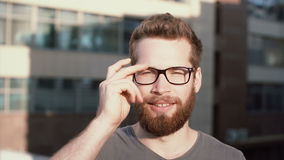 Portrait of young man with beard standing in front of sun and blinking. Attractive businessman takes off the glasses. stock video