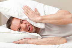 Portrait of Young man in bed angry about noise Stock Image