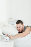 Portrait of a young man being awakened by an alarm clock Royalty Free Stock Photo