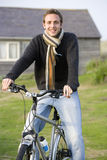 Portrait of young man on bicycle outdoors Stock Image