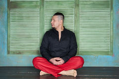 Portrait of a young man, black shirt and red slacks, lotus posture Royalty Free Stock Photography