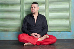 Portrait of a young man, black shirt and red slacks, lotus posture Stock Images