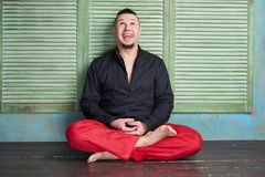 Portrait of a young man, black shirt and red slacks, lotus posture Royalty Free Stock Photo