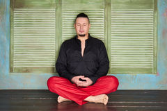 Portrait of a young man, black shirt and red slacks, lotus posture Stock Photos